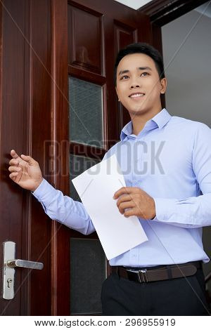 Young Asian Man With Resume Standing In Entrance Of Employer Office And Knocking On Wooden Door