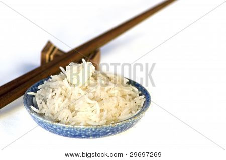 Blue bowl of rice and wooden chopsticks.