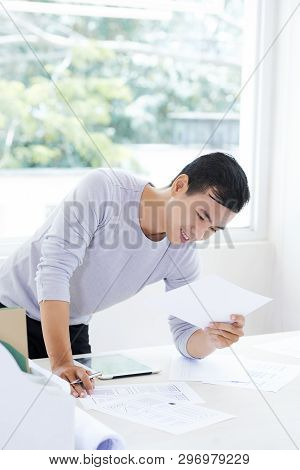 Cheerful Handsome Young Asian Designer In Gray Sweater Standing At Table In Office And Analyzing Ske