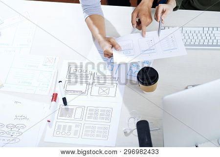 Close-up Of Unrecognizable Creative Colleagues Pointing At Sketch And Discussing Ux Design For Mobil