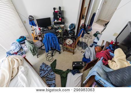 Very messy, cluttered,teenage boy's bedroom with piles of clothes, electronics, music and sports equipment.