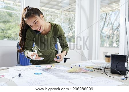 Cheerful Asian Female App Developer With Ponytail Standing At Table With Design Tools And Working Wi