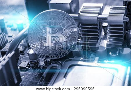 Silver bitcoin on the motherboard, closeup view. Business concept of digital cryptocurrency. Blockchain technology, bitcoin mining concept