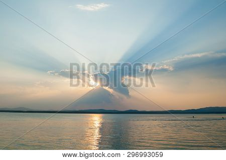 Summer sunset landscape - summer sea waters lit by sunset summer light. Summer sunny water scene in colorful tones. Sea summer natural landscape