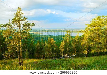 Forest summer landscape with mixed summer forest trees on the mountain slopes and lake under soft sunset light - mountain forest summer nature. Summer colorful mountain background