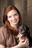An attractive young woman poses with her adorable Yorki-poo puppy poster