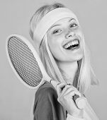 Tennis club concept. Girl adorable blonde play tennis. Sport for maintaining health. Athlete hold tennis racket in hand on grey background. Active leisure and hobby. Tennis sport and entertainment poster