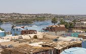 View of river Nile in Aswan Egypt from riverbank through rural countryside landscape with traditional Nubian village houses in foreground poster