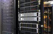 Server rack with working mainframe disk storage and yellow LED indicator inside poster