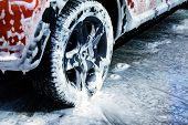Car wheel close up. Car is cleaning with soap suds at self service car wash. White lather on auto. poster