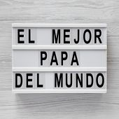 'El Mejor Papa Del Mundo' words on a lightbox over white wooden background, top view. Overhead, from above, flat lay. poster