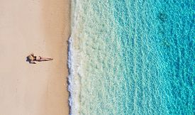 Aerial View Of A Girl On The Beach On Bali, Indonesia. Vacation And Adventure. Beach And Turquoise W