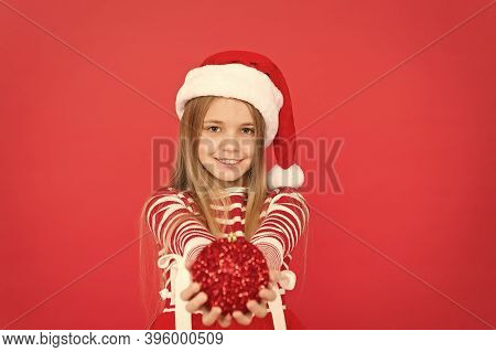 Its Xmas Season. Happy Child Hold Xmas Tree Ball. Little Girl Smile In Xmas Costume Red Background.