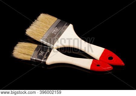 Two Paintbrushes For Construction And Redecoration Isolated On Black Reflective Background