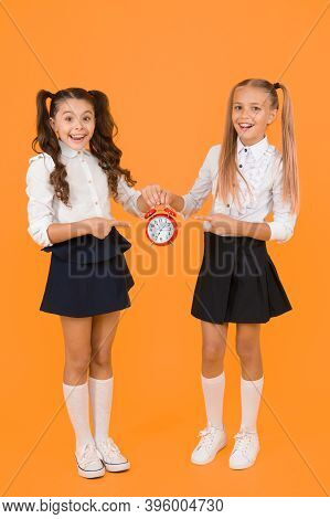 This Clock Is Perfect. Happy Little Girls Pointing At Vintage Alarm Clock On Yellow Background. Smal
