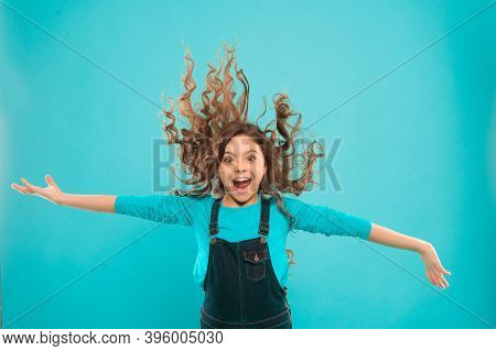 Feeling Active And Energetic. Energetic Little Girl With Long Brunette Hair On Blue Background. Acti