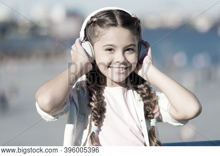 Going With The Flow. Adorable Headset User. Small Child Wearing Adjustable White Headset. Little Gir
