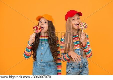 Having A Lick. Little Girls Enjoying Delicious Taste Of Lollipops On Yellow Background. Small Childr