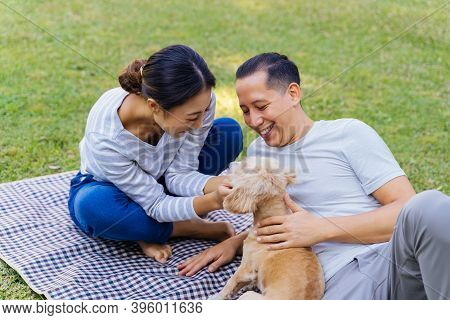 Young Adult Asian Couple Playing A Puppy With Green Grass Outdoors In Background. 30s Mature Man And