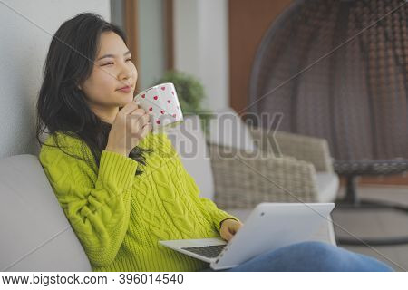 Young Asian Woman With Headset Drinking Cup Of Tea And Browsing Social Media. . High Quality Photo