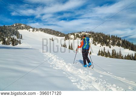 Active Backpacker Woman In Fresh Powder Snow, Ski Touring On The Deep Snow. Backcountry Skier With C