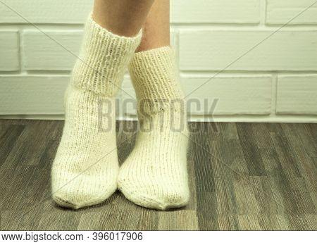 Handmade Socks From White Threads, Crocheted Socks Close-up. Photo Of A Girl's Legs In Knitted Socks