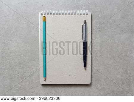 A Spring Notebook With A Sheet Of Craft Paper A5 With A Ballpoint Pen And Simple Green Graphite Penc
