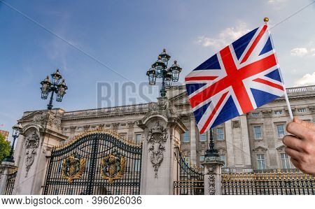 Toursist In London Holding Flag Of Great Britain In Hand. Buckingham Palace In Background.
