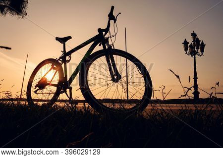 Silhouette Of A Bike At Sunset. The Sun Shines Through The Bicycle Wheel With Silhouette Of Big Vint