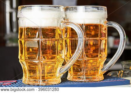 Two Glasses Of Fresh Foamy Beer On The Bar Counter