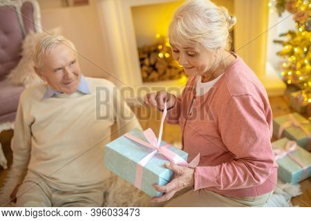 Elderly Woman Opening Christmas Gift From Her Husband And Looking Anticipated