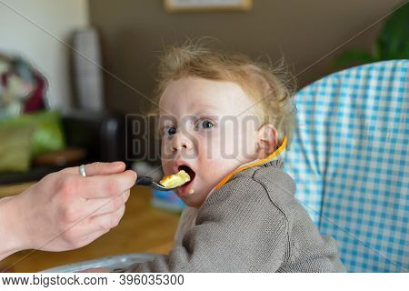 Portrait Of A Baby Eating With A Spoon