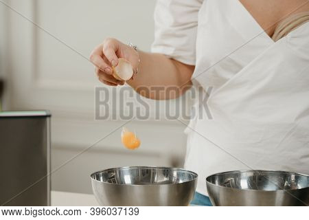 A Photo Of The Hand Of A Woman Who Is Dropping The Yolk Of The Organic Farm Egg To The Stainless Ste