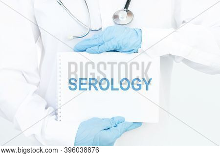 Doctor Holds A Card With The Name Of The Diagnosis Serology. Medical Concept.
