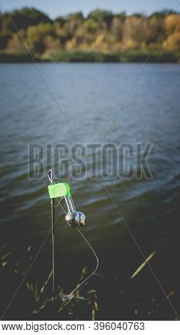 Fishing Bottom Tackle With Green Bell On The Lake Shore In Autumn. Toned Photo With The Vignetting.