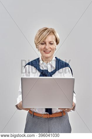 Portrait Of Elegant Middle Aged Caucasian Woman Wearing Business Attire Holding Laptop, While Having