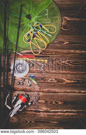 Fishing Tackle On A Wooden Background. Studio Photo With Vignetting.