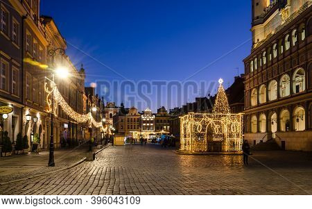 Poznan / Poland - 2019: A Christmas Tree Glittering With Colorful Lights And A Christmas Market On T