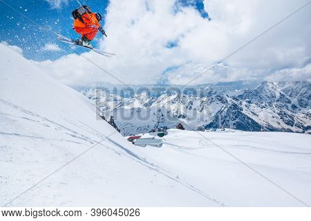 Professional Athlete Skier Freerider In An Orange Suit With A Backpack Flies In The Air After Jumpin