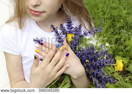 Beautiful Blonde Girl Holding A Bouquet Of Meadow Wildflowers In Summer.children Is Fashionable Mani