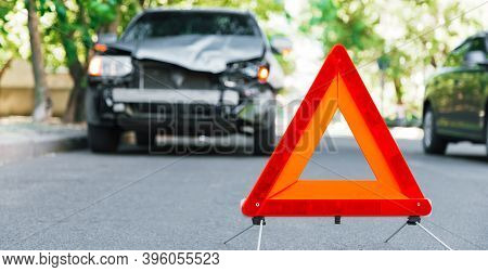 Red Emergency Stop Triangle Sign On Road During A Car Accident. Broken Gray Car During Road Traffic