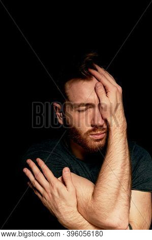 A Man On A Black Background Covers His Face With His Hands. The Atmosphere Of Hopelessness, Dejectio