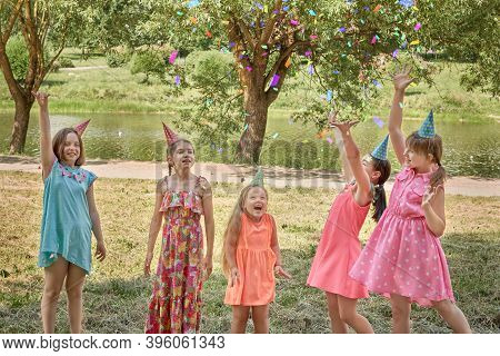 Girls Throw Up Confetti At A Childrens Party In A Summer Park.
