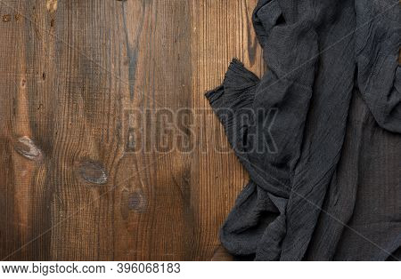Black Gauze Kitchen Napkin On A Brown Wooden Table, Copy Space