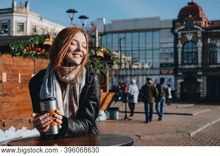 Young Redhead Woman Enjoying The Sun And Drinking Take Away Coffee Wandering On Winter City Streets