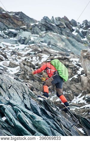 Brave Alpinist Holding Rope While Climbing Alpine Ridge. Young Climber With Backpack Ascending Mount