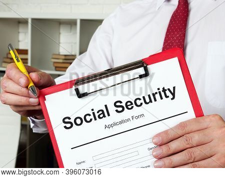 The Clerk Offers A Social Security Benefits Form To Fill In.