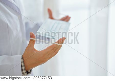 Hands Of Medical Worker In Labcoat Putting On Protective Mask