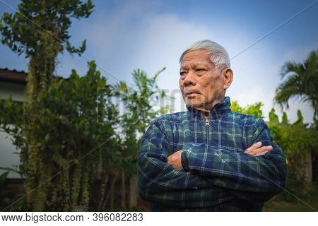 Portrait Of Elderly Asian Man Arms Crossed And Looking Away While Standing In A Garden. Space For Te