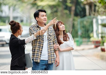 Vietnamese Real Estate Agent Showing Houses To Young Couple